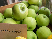 Close up green apple with tag in crate