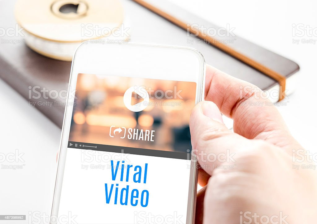 Close up hand holding smart phone with Viral Video word stock photo