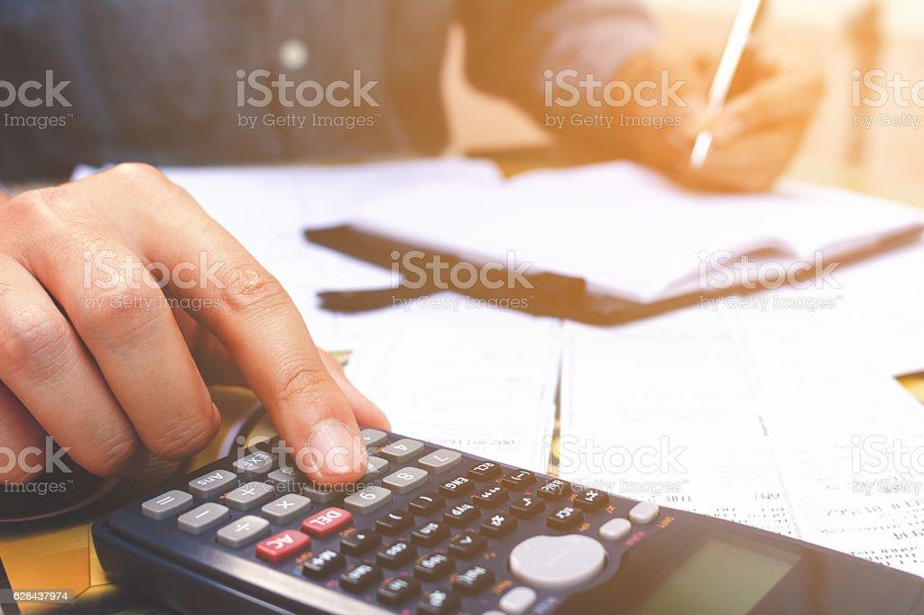 Close up hand man using calculator and make note stock photo
