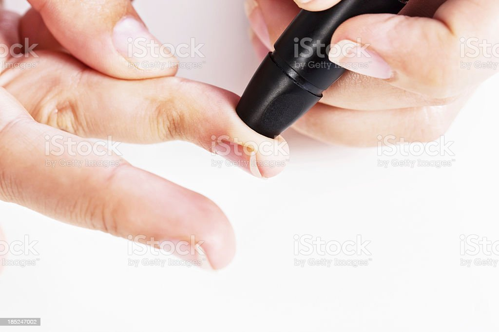 Close up hand pressing lancet on finger to draw blood stock photo