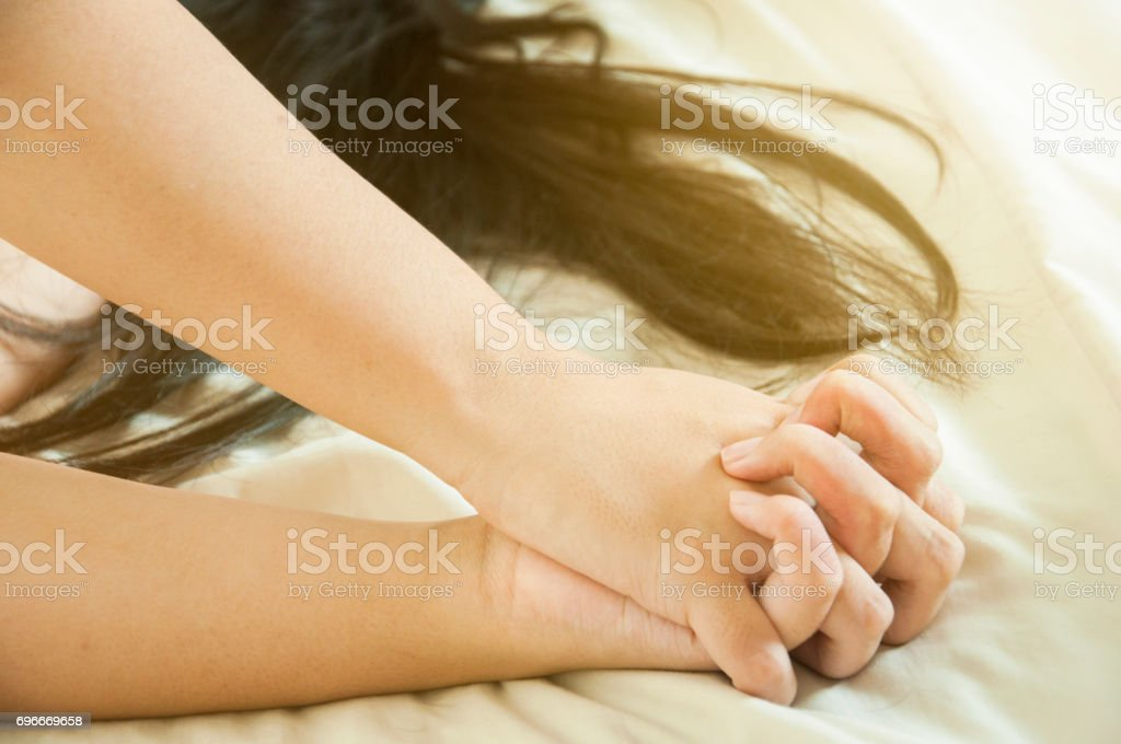 Close up hands of a couple make love hot sex on a bed stock photo