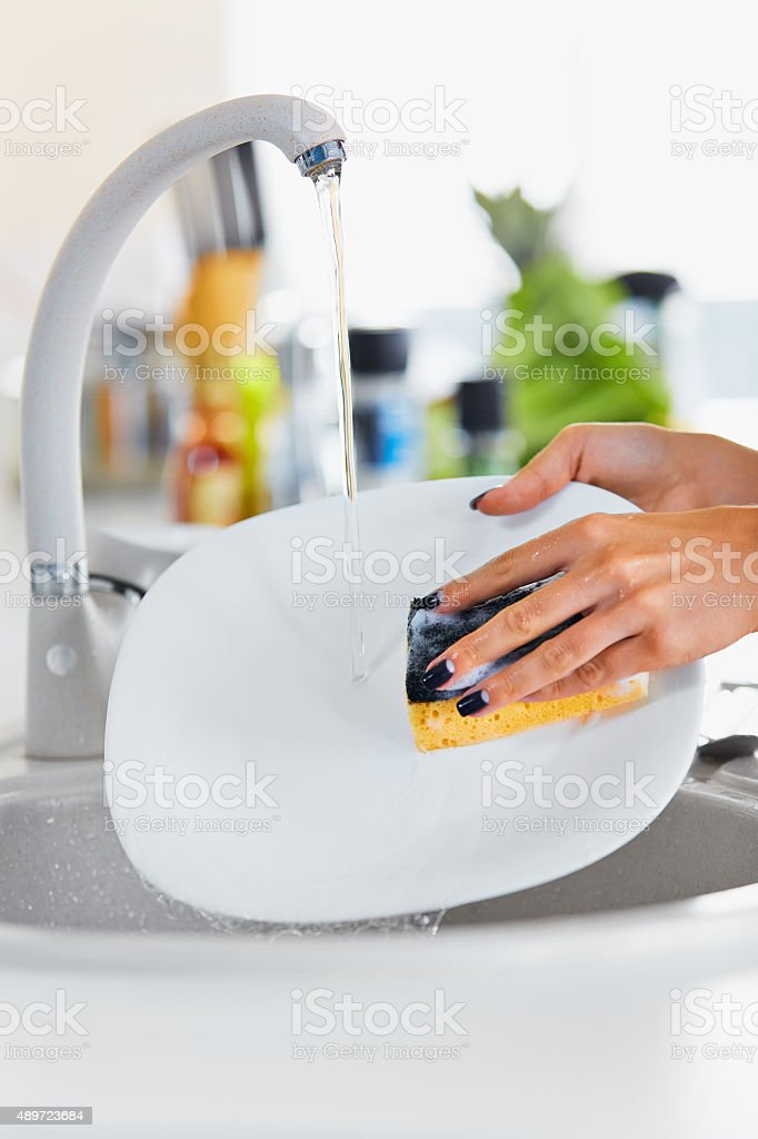 Close up hands of woman washing dishes in the kitchen stock photo