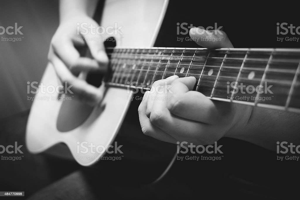 Close up hands playing acoustic guitar stock photo