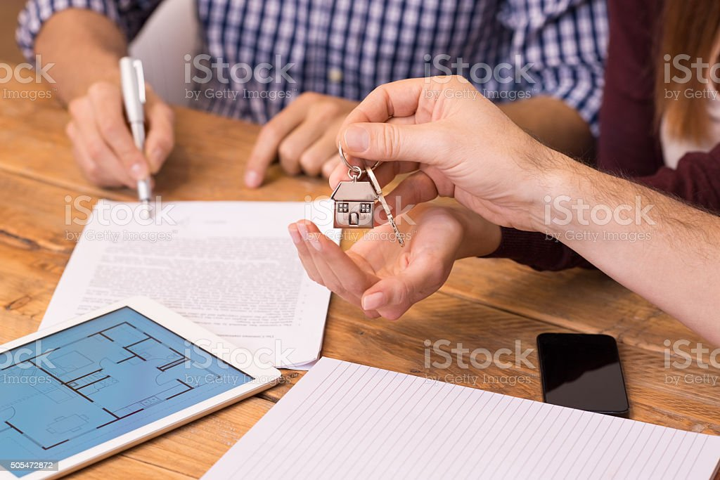 Close up hands receiving house keys stock photo