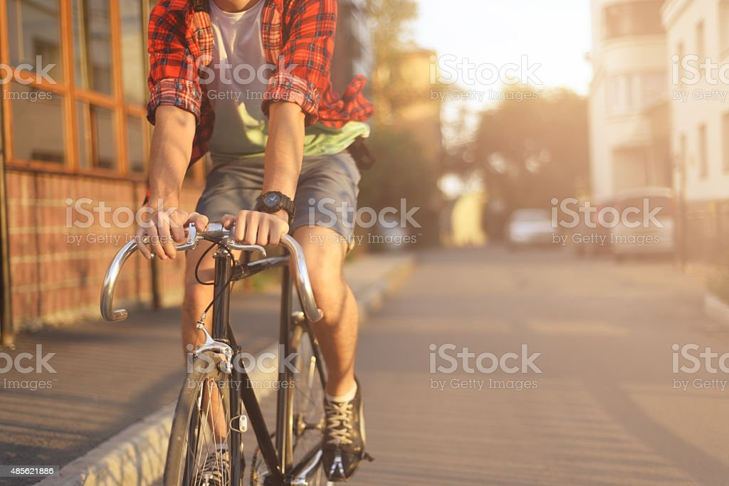 Close up hipster on bike in the city at sunset. Shot with sunflare...