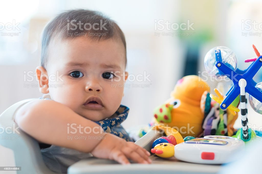 Close up hispanic infant boy, baby chair with toys stock photo