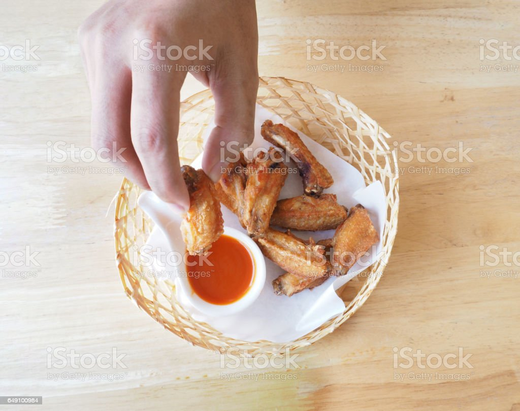 Close up human's hand pick fried chicken up and dip in sauce. stock photo