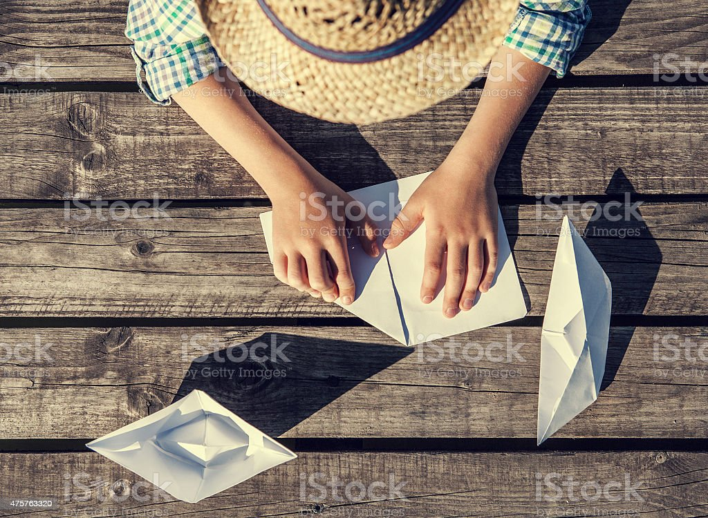 Close up image boy hands making a paper boats stock photo