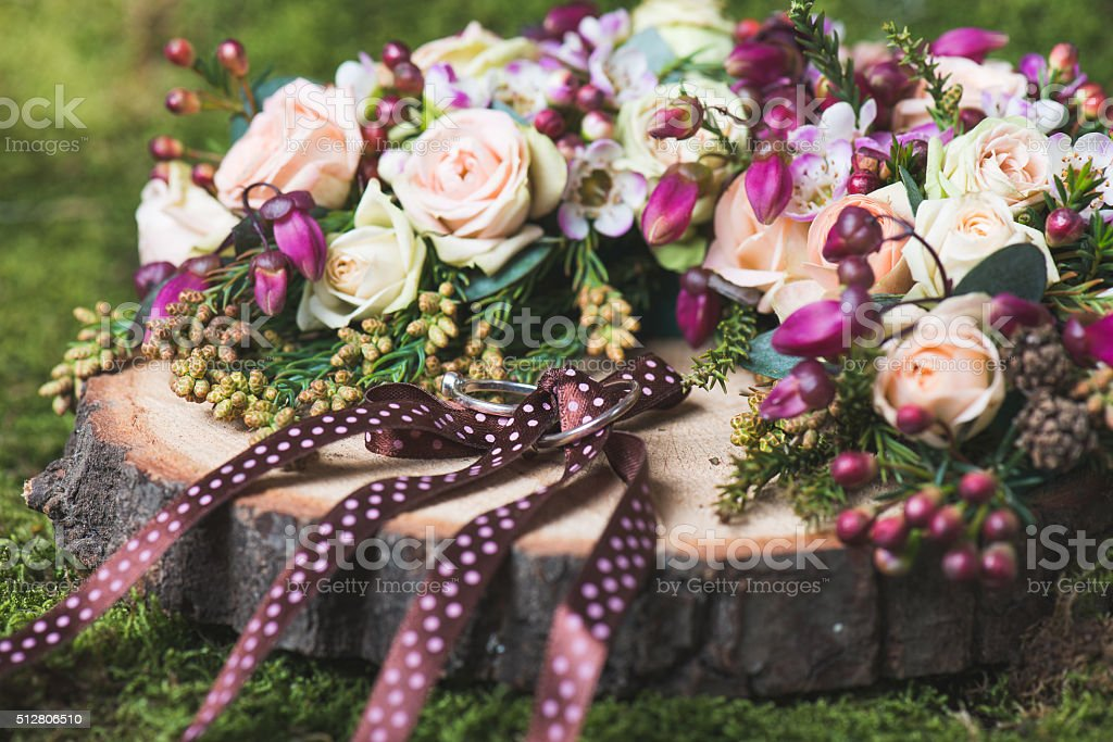 Close up image of wedding rings on decorated wooden base. stock photo