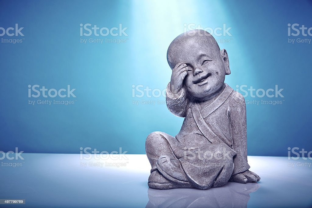 Close Up Laughing Stone Buddah Isolated On Blue Background stock photo