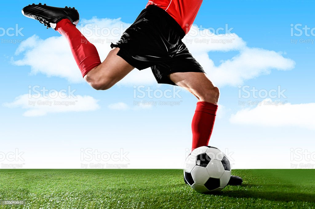 close up legs football player in red socks kicking ball stock photo