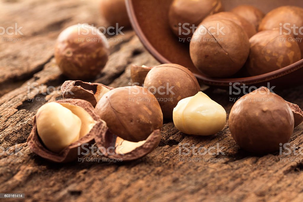 Close up macadamia nuts on wooden plate stock photo