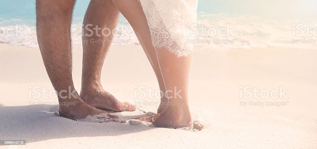 Close up male and female feet on the sand stock photo