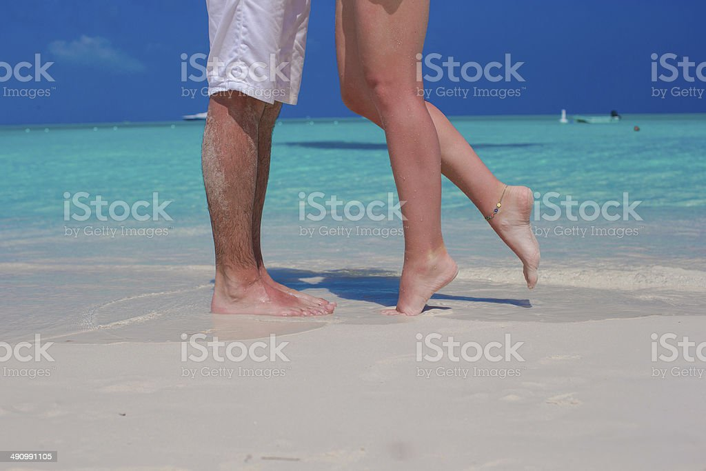 Close up male and female feet on white sand royalty-free stock photo