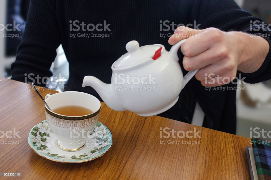 Close up male hands pouring hot tea stock photo