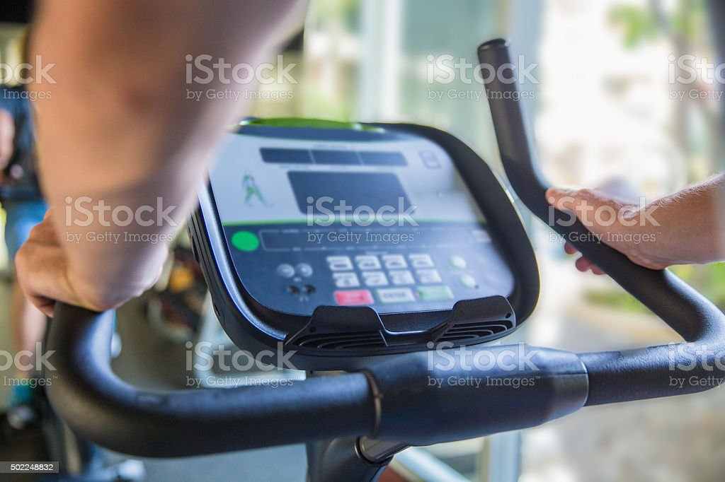 Close up males hand holding bicycle - spinning at  gym stock photo