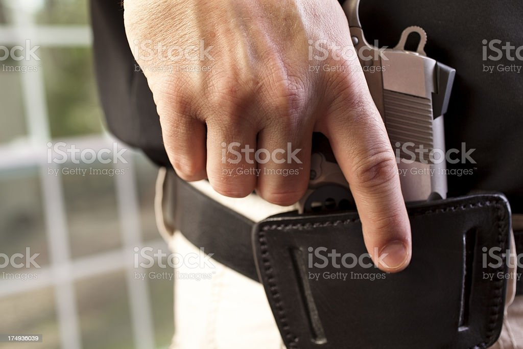 Close up  man drawing weapon gun pistol from leather holster stock photo
