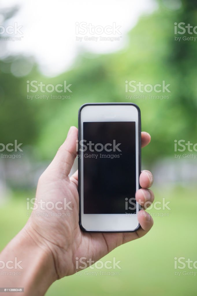Close up man hand using smartphone in green park stock photo