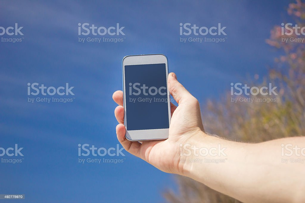 Close up man hands holding smartphone, taking blue sky picture stock photo