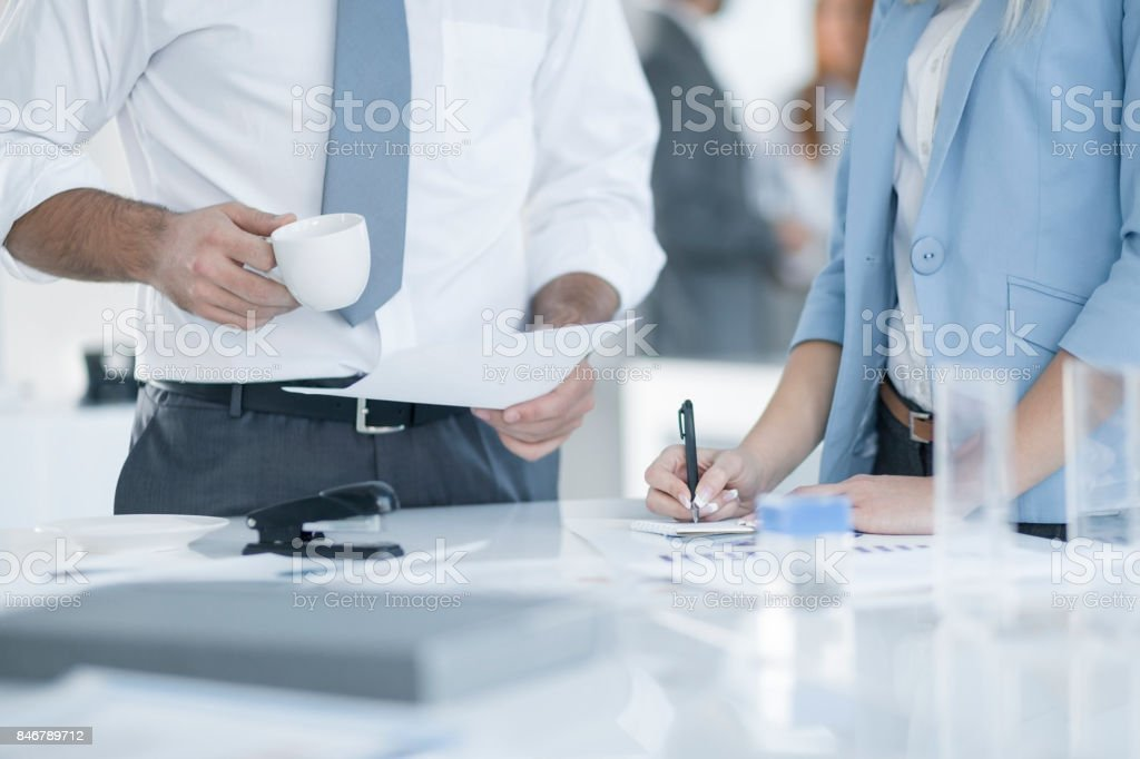 Close up, man holding cup of coffee and woman writing on notebook. stock photo
