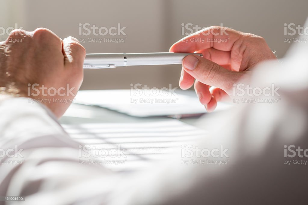 Close up Man Leaning on the Table Holding a Pen stock photo