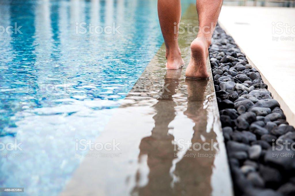 Close up man walking barefoot next to hotel swimming pool stock photo