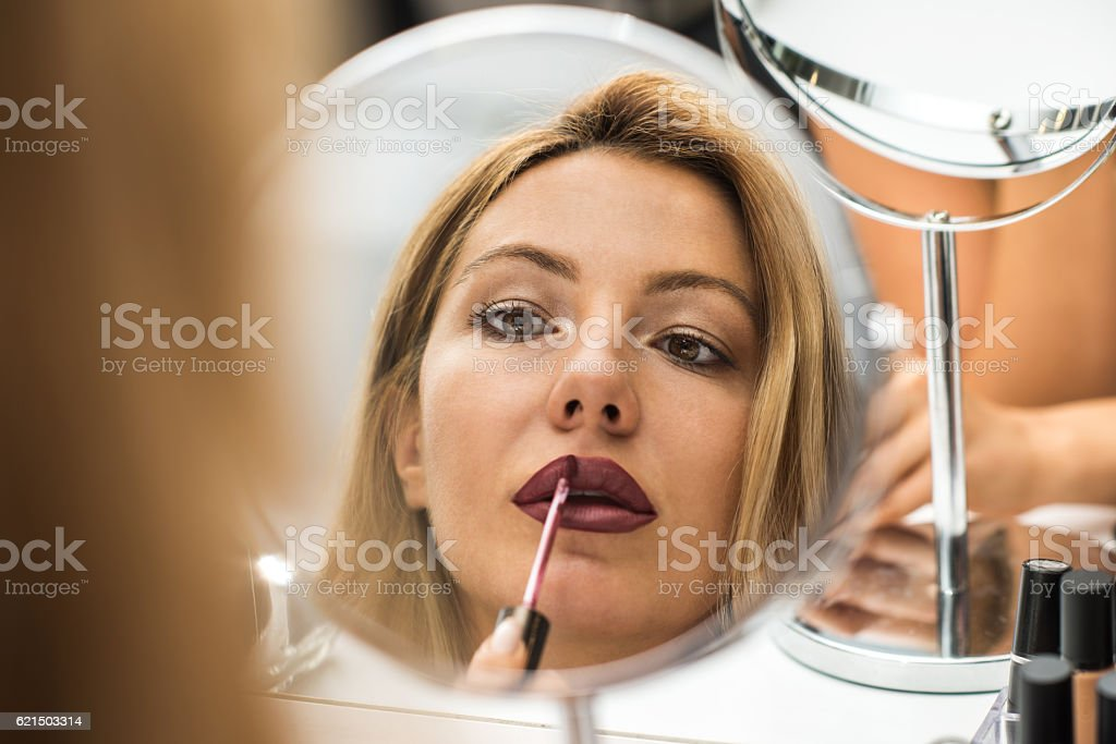Close up mirror reflection of young woman applying lip balm. stock photo