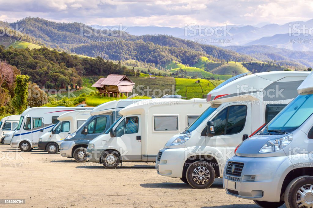 Close up motorhomes parked in a row on background green terraced rice field nature landscape. stock photo