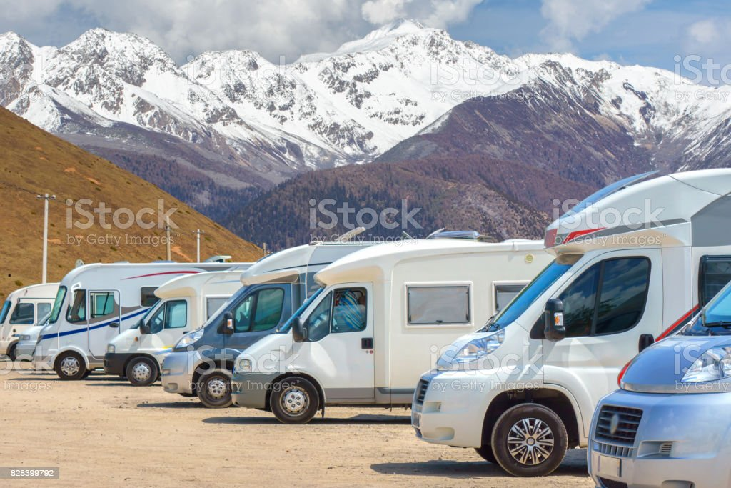 Close up motorhomes parked in a row on background snow mountain nature landscape. stock photo