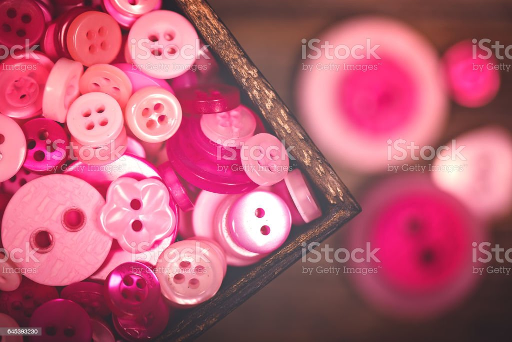 A close up of a box of pink and white buttons stock photo