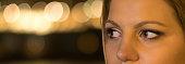 Close up of a brown woman eyes night lights bokeh.
