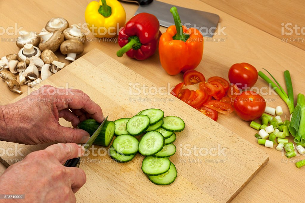 Close up of a chefs hands slicing an English cucumber stock photo