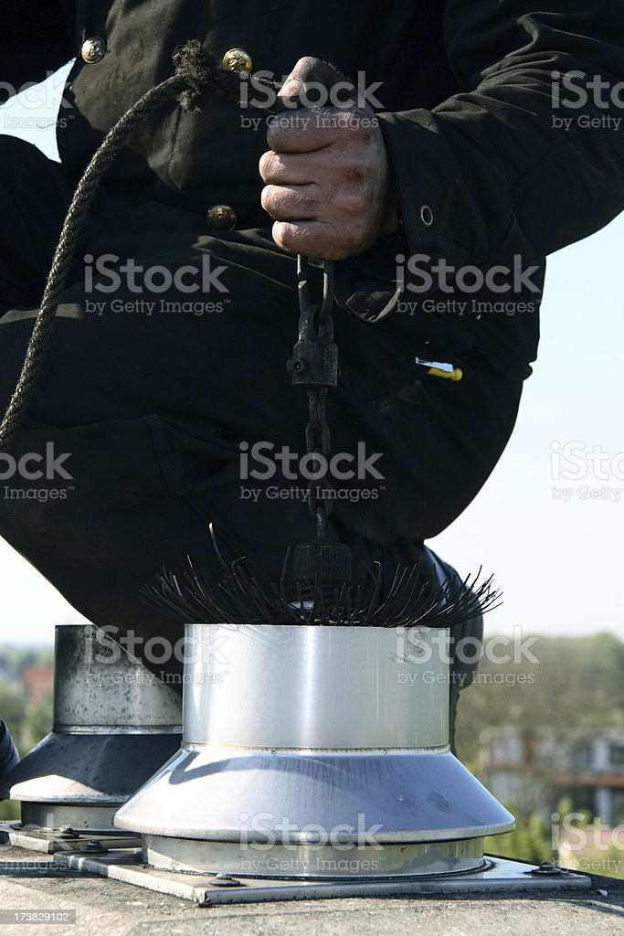close up of a chimney sweep on the roof stock photo