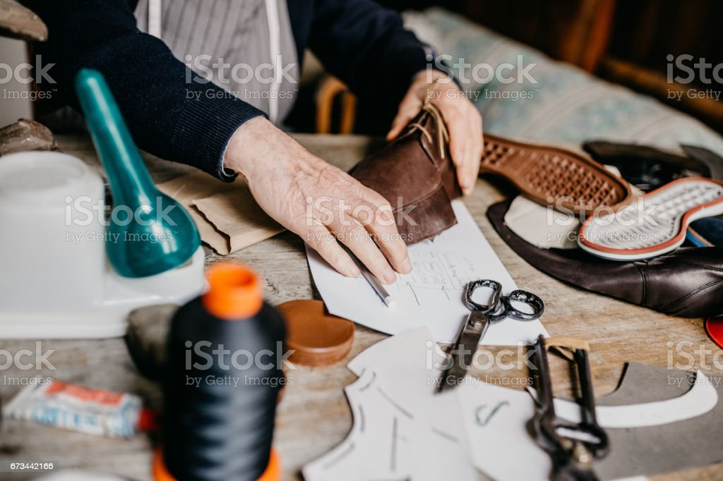 Close up of a cobbler making a shoe for men stock photo