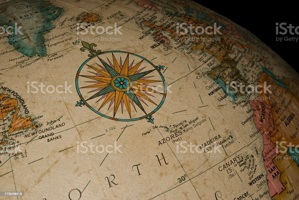 A close up of a compass on a globe stock photo