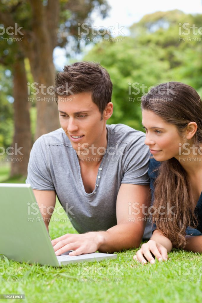Close up of a couple using laptop while lying royalty-free stock photo