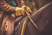 Close up of a cowboy holding reins in his hands