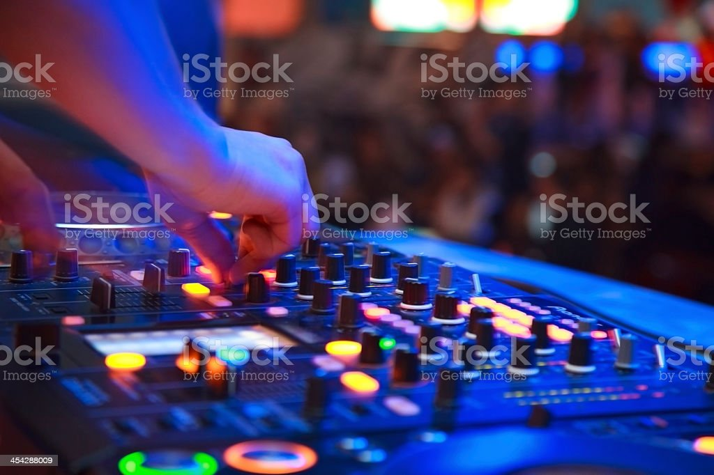 A close up of a DJ's hands using a mixing board at a club stock photo