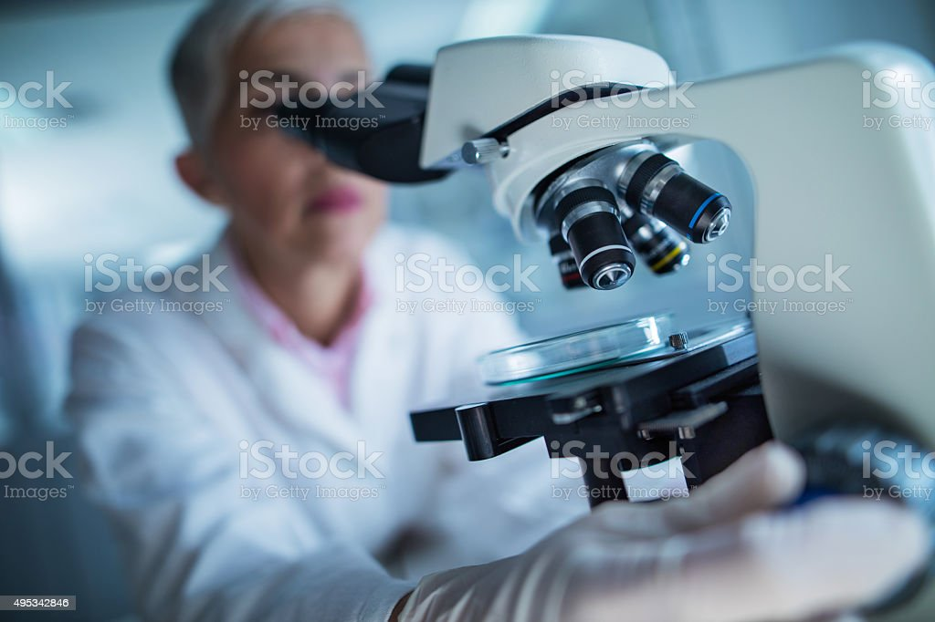 Close up of a doctor using microscope. stock photo
