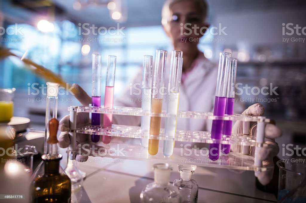 Close up of a female chemist holding test tubes. stock photo