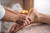 Close up of a foot massage with candles in background