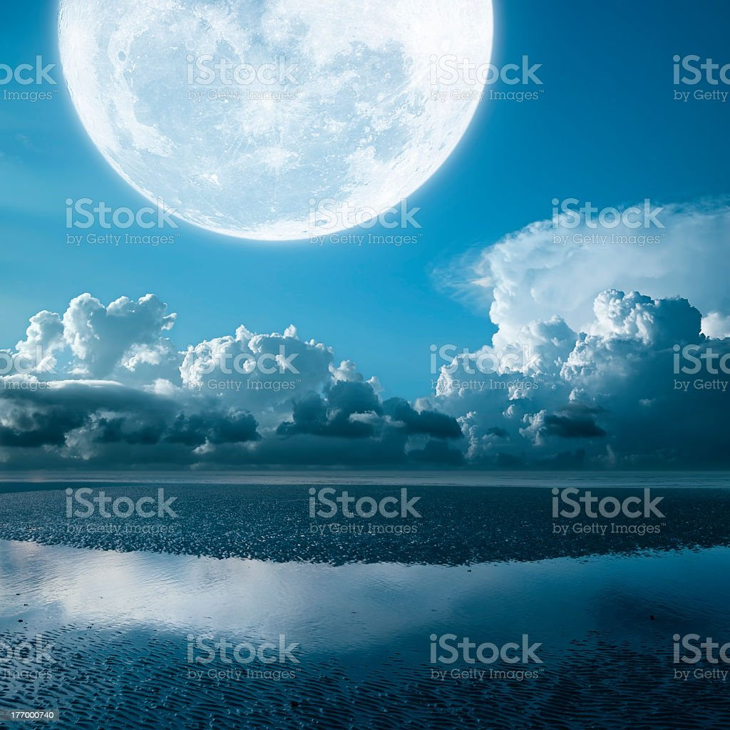 Close up of a full moon over the beach stock photo