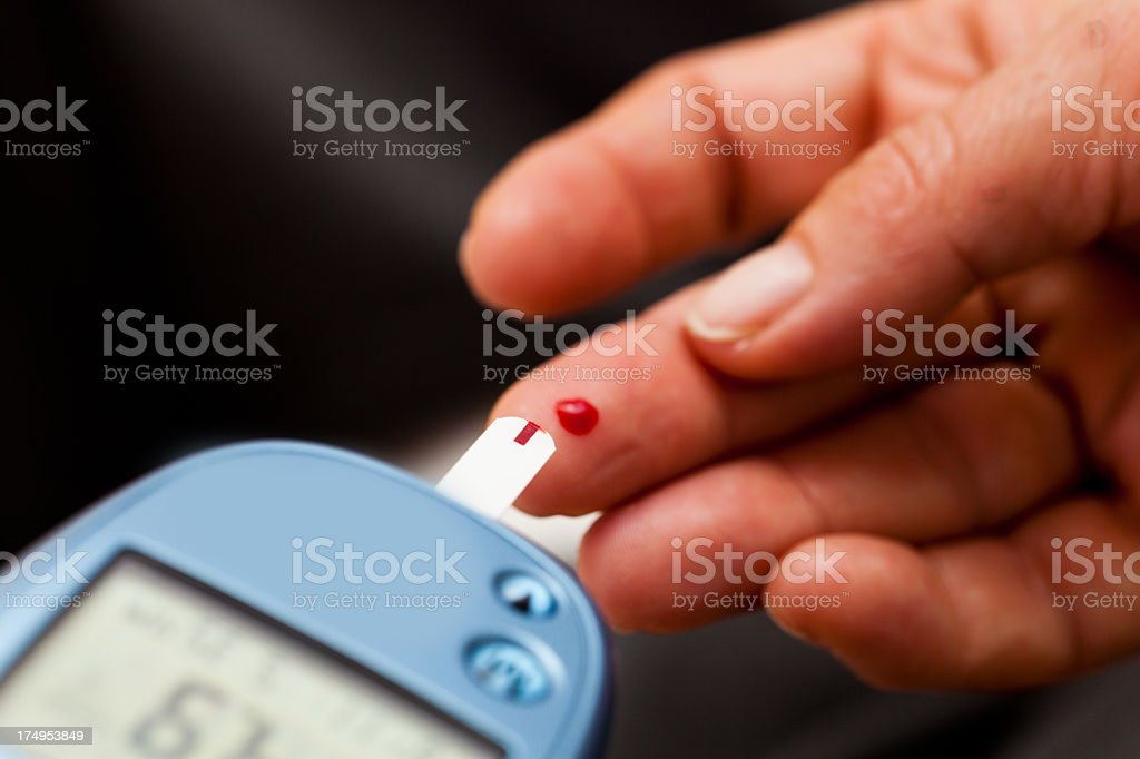A close up of a glucose blood test being taken with monitor stock photo