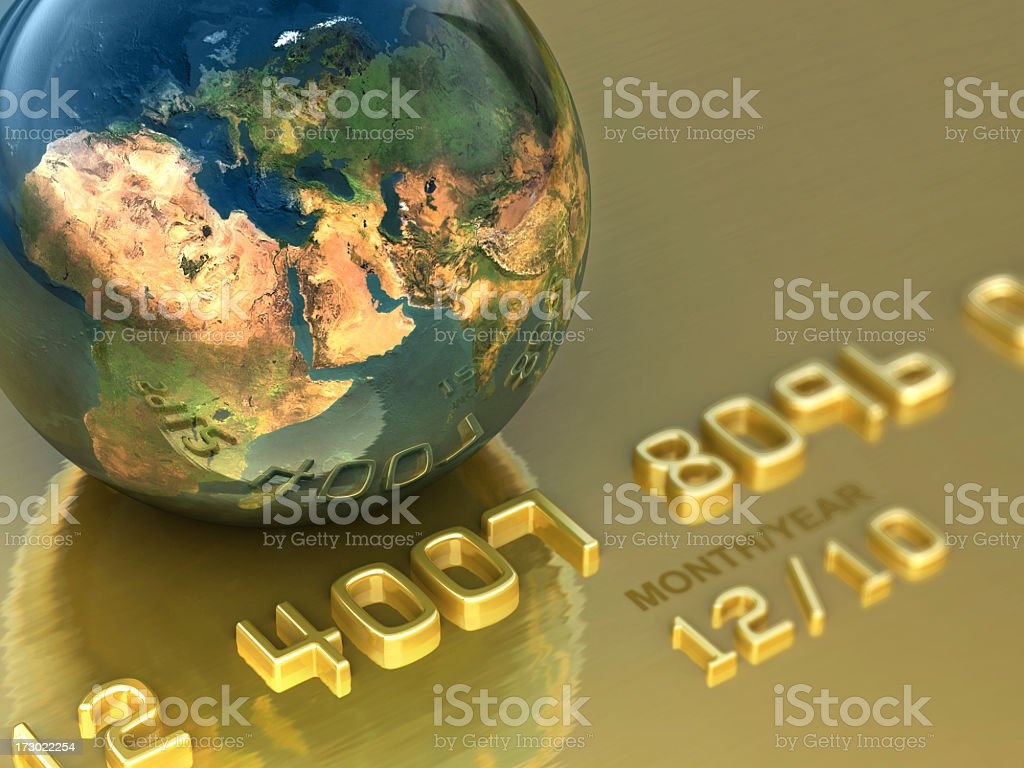 A close up of a gold credit card beneath a small globe stock photo