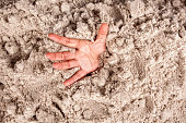 Close up of a hand coming out of deep sand