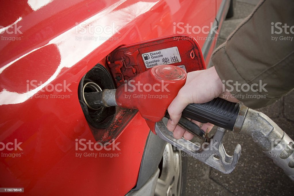 Close up of a hand filling up his car with diesel stock photo