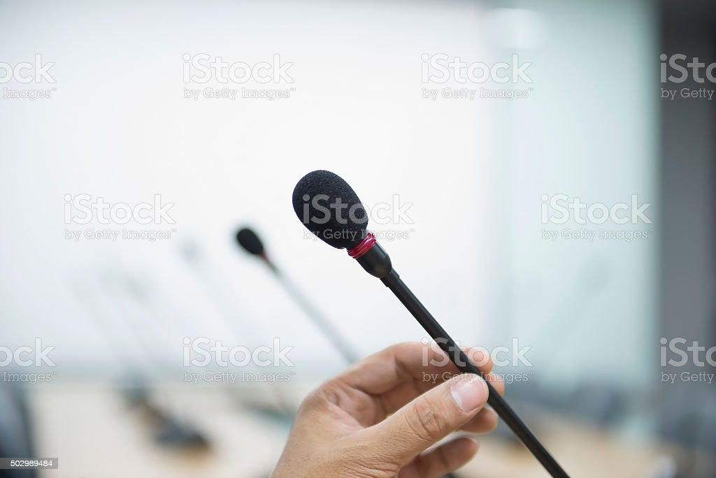 Close up of a hand holding a business conference microphone stock photo