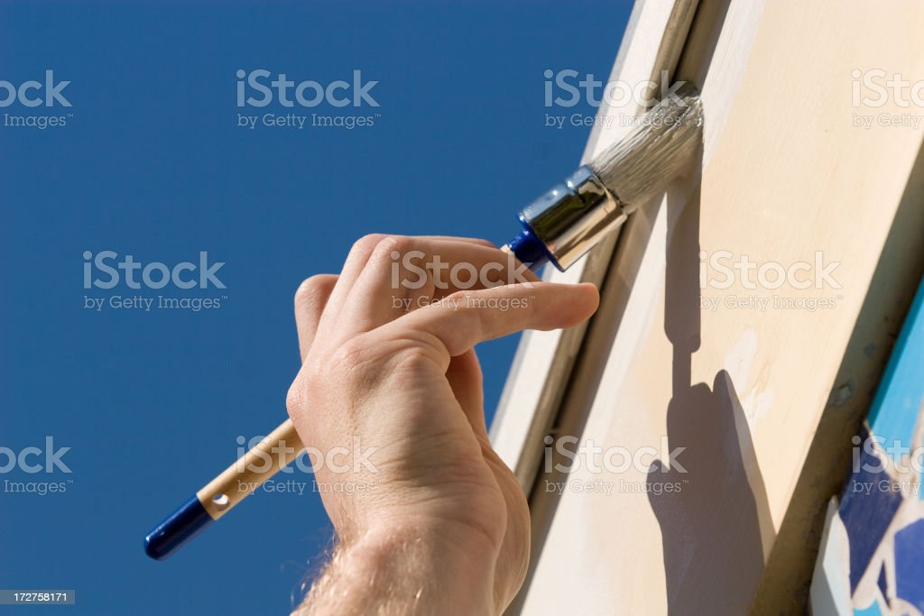 Close up of a hand painting a white fence royalty-free stock photo