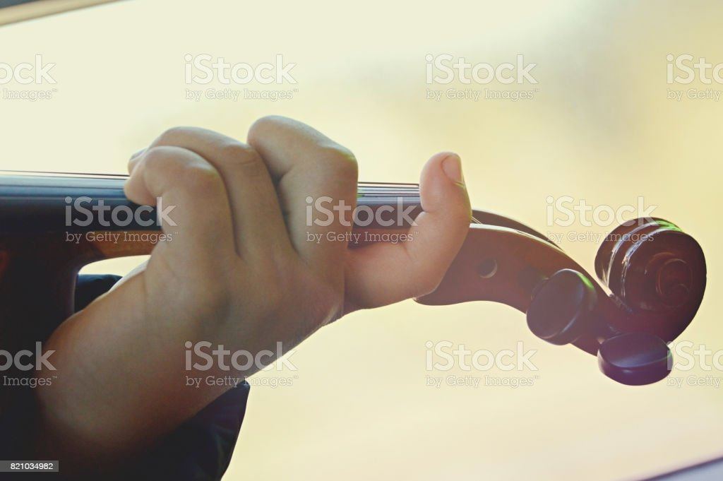 Close up of a hand playing the violin fingerboard. stock photo