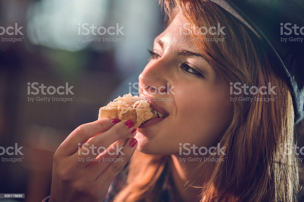 Close up of a happy woman biting a sandwich. stock photo